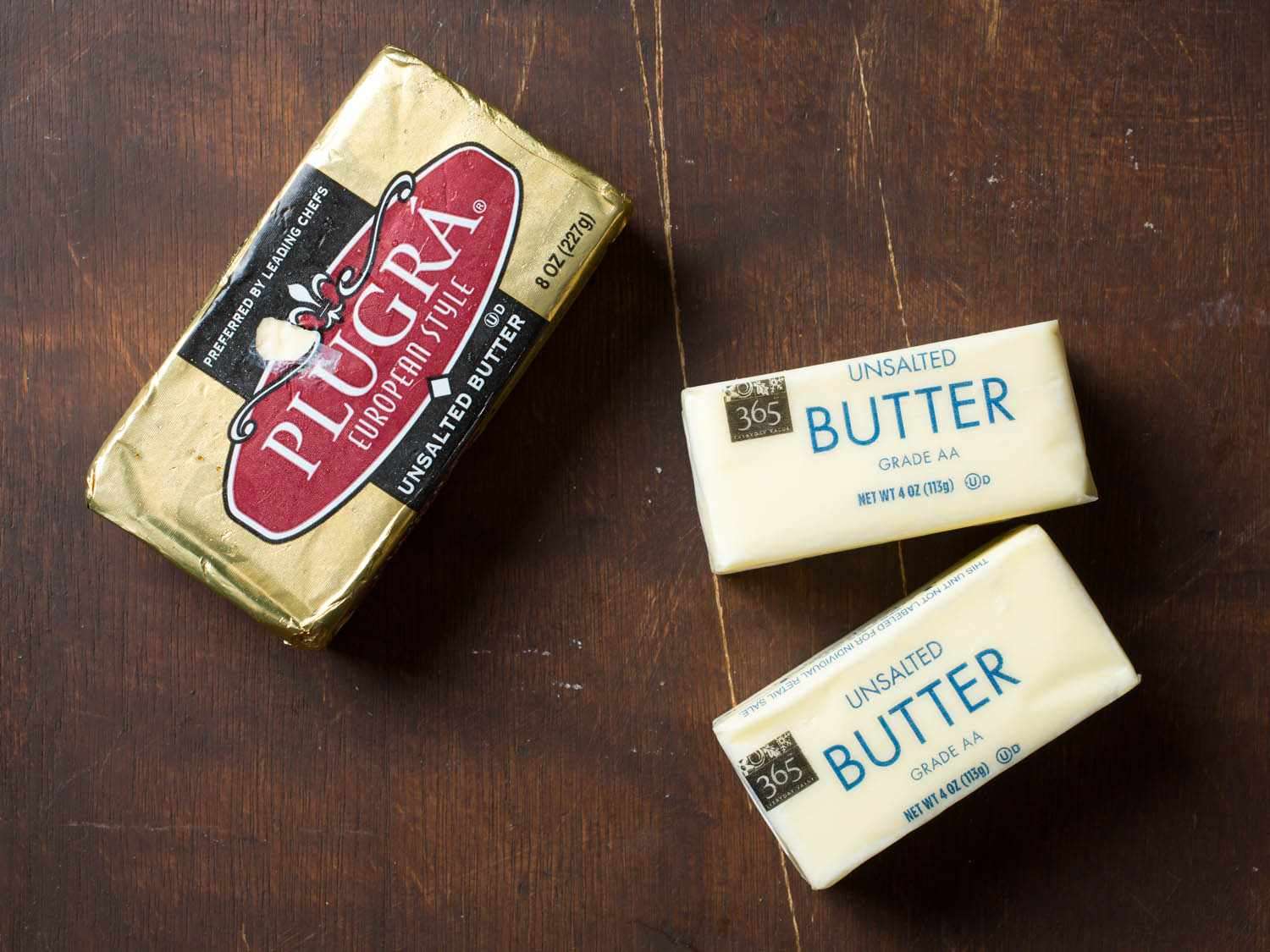 Overhead shot of three packages of butter (Plugra European-style butter and two packages of American-style unsalted butter) on a wooden background
