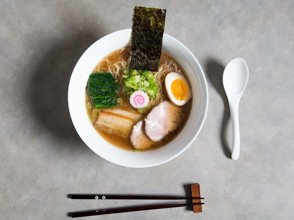 Overhead shot of a bowl of shoyu ramen, garnished with meats, seaweeds, fish cake, and egg, next to a spoon and a pair of chopsticks