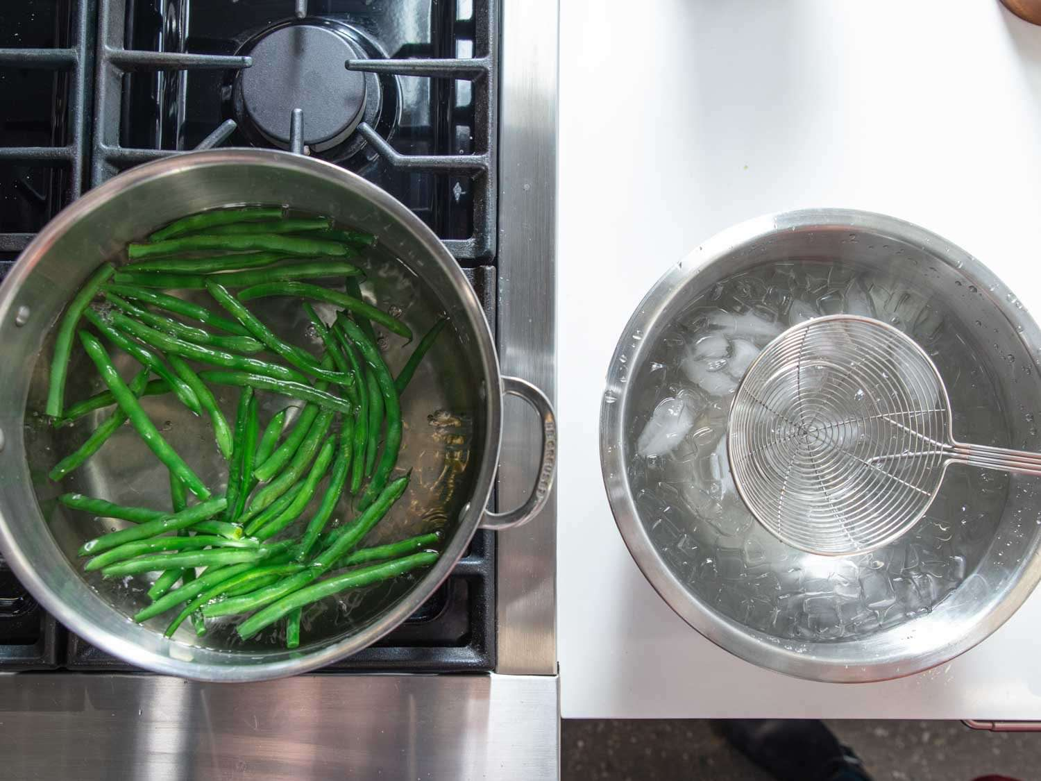 Overhead of green beans cooking in a pot of boiling water with an ice bath set up next to the stove.