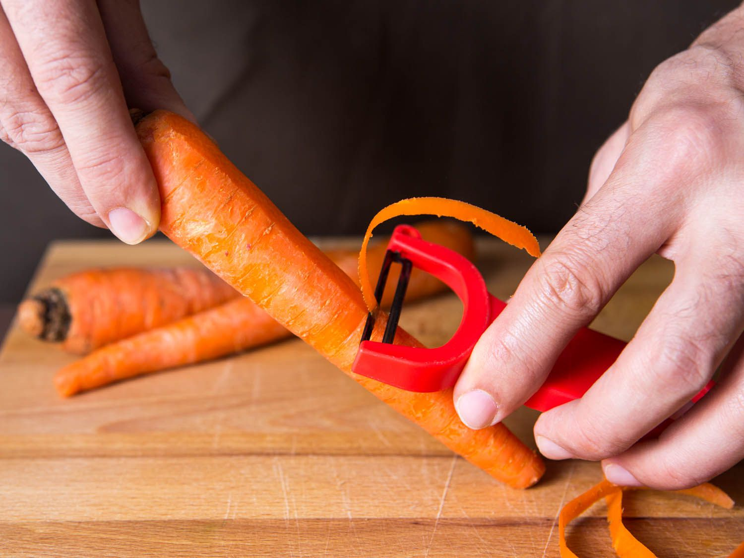 Using a y-peeler to peel a carrot
