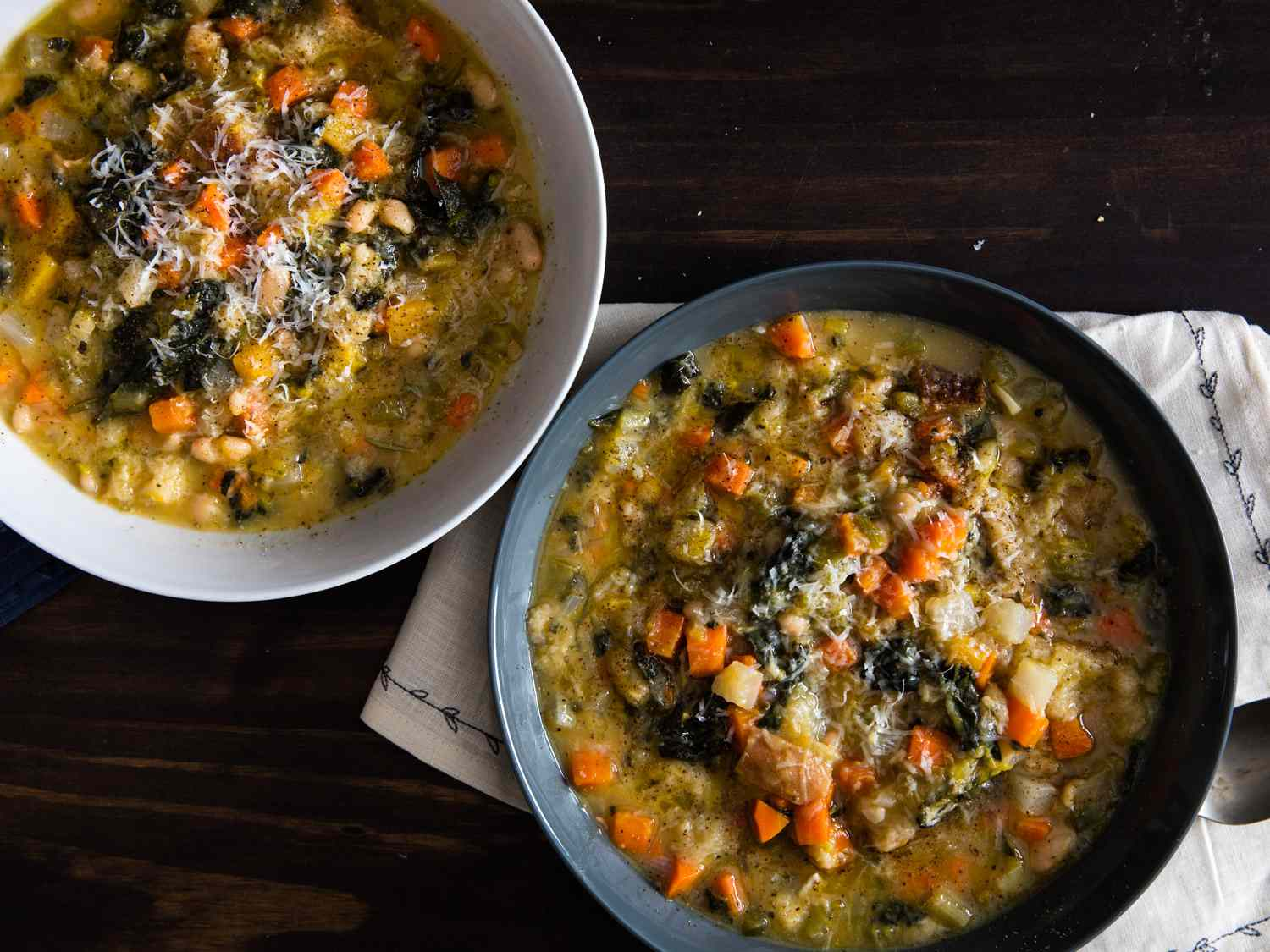 two bowls of Ribollita (Hearty Tuscan Bean, Bread, and Vegetable Stew) on a dark wood table.