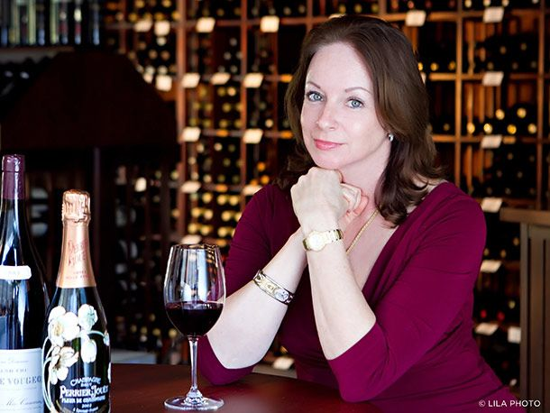 Sommelier with a glass of red wine, surrounded by bottles of wine