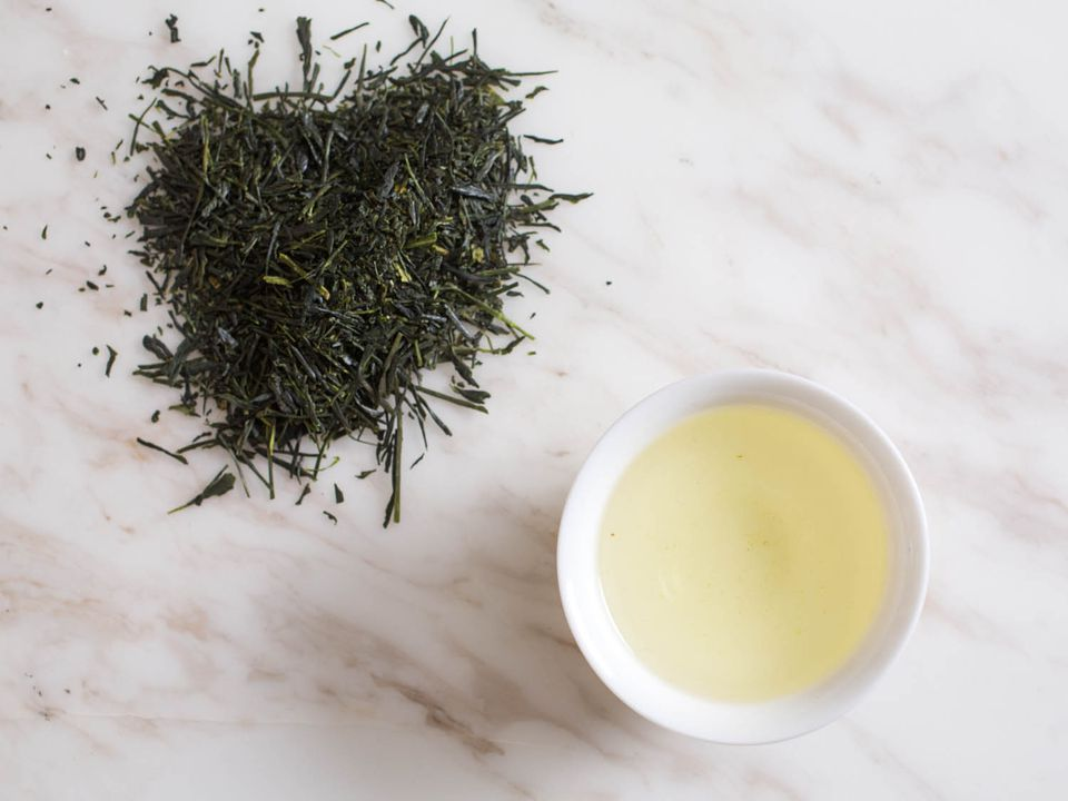 A pile of green tea leaves on a marble countertop, next to a small bowl of brewed green tea.