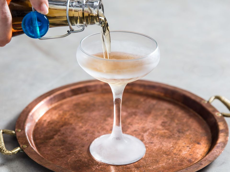 Pouring the Three Piece Suit Cocktail into a chilled coupe glass