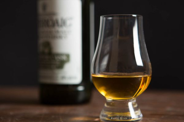 A glass of Islay Scotch whisky, with a bottle in the background.