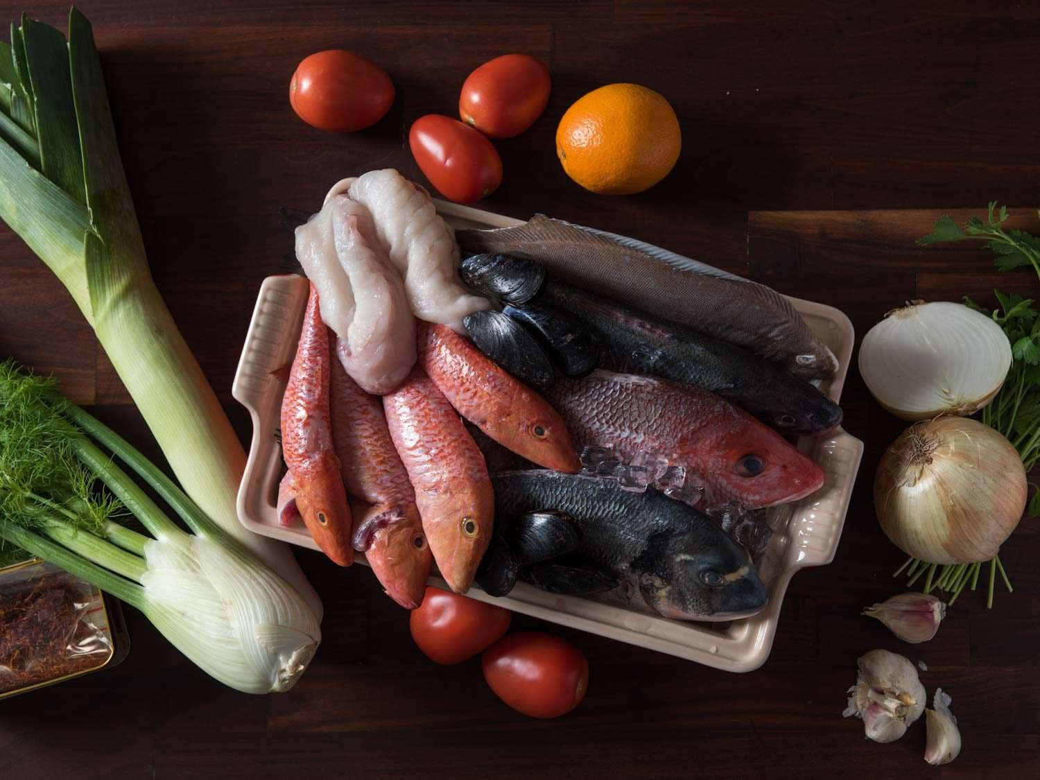 The ingredients used for bouillabaisse: mixed fish, fennel, onion, garlic, tomato, orange, saffron, and more.