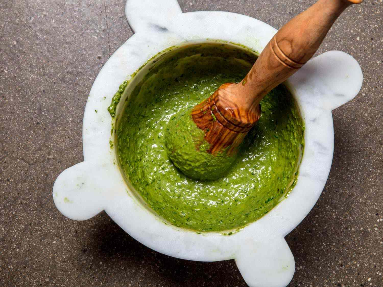 Finished pesto in a marble mortar and pestle