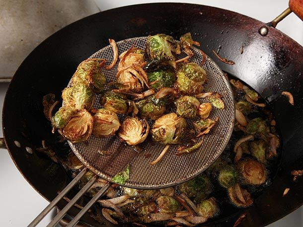 Deep fried Brussels sprouts and shallots lifted from a wok with a metal spider.