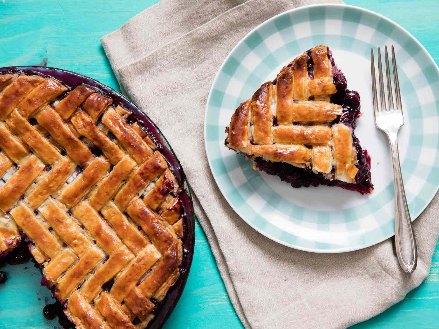 A slice of herringbone lattice–topped blueberry pie on a plaid-rimmed plate with a fork, next to the rest of the pie