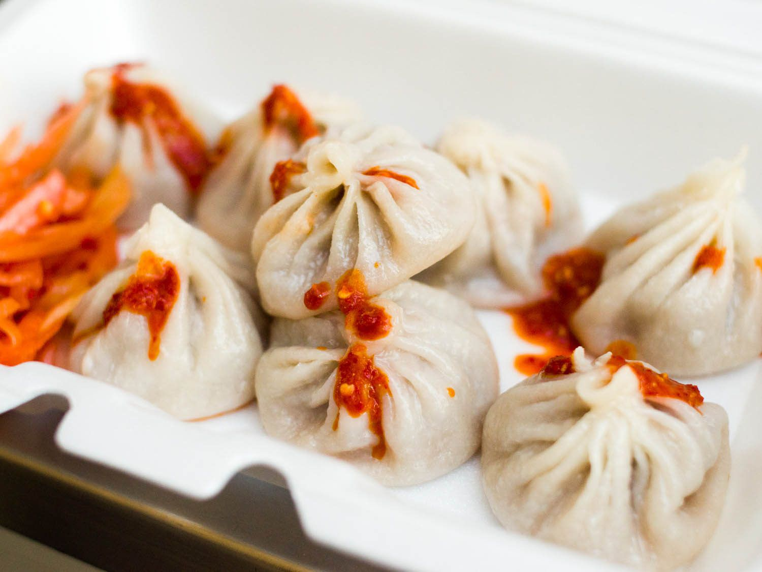 Close-up of momos (round Tibetan dumplings) dressed with chili sauce, on a white dish