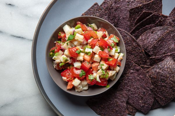 hearts of palm salsa with blue corn chips on a plate