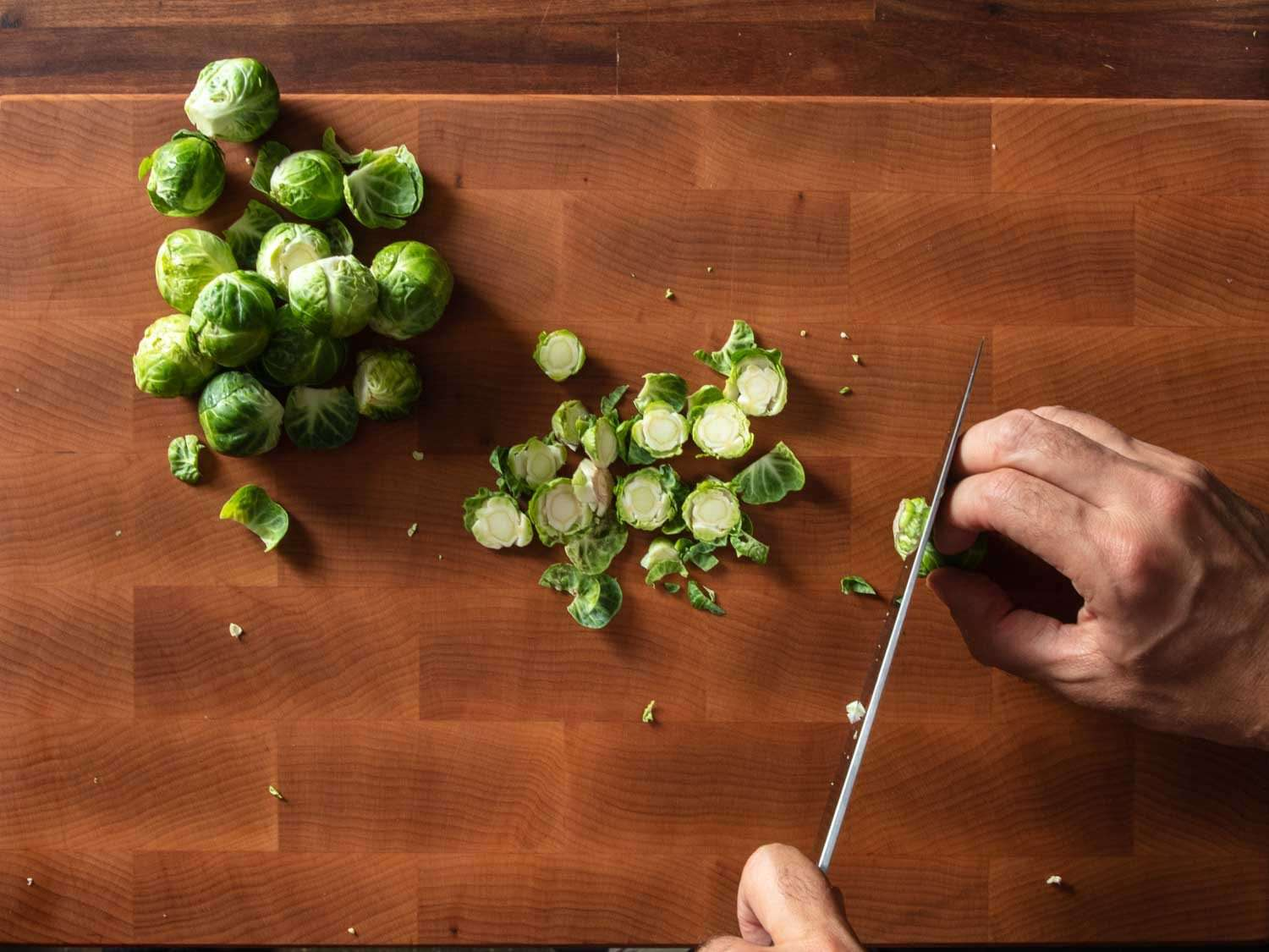 A top-down view of a cutting board loaded with a pile of Brussels sprouts; you can see the cook's hands holding a chef's knife and trimming away the base of each sprout efficiently