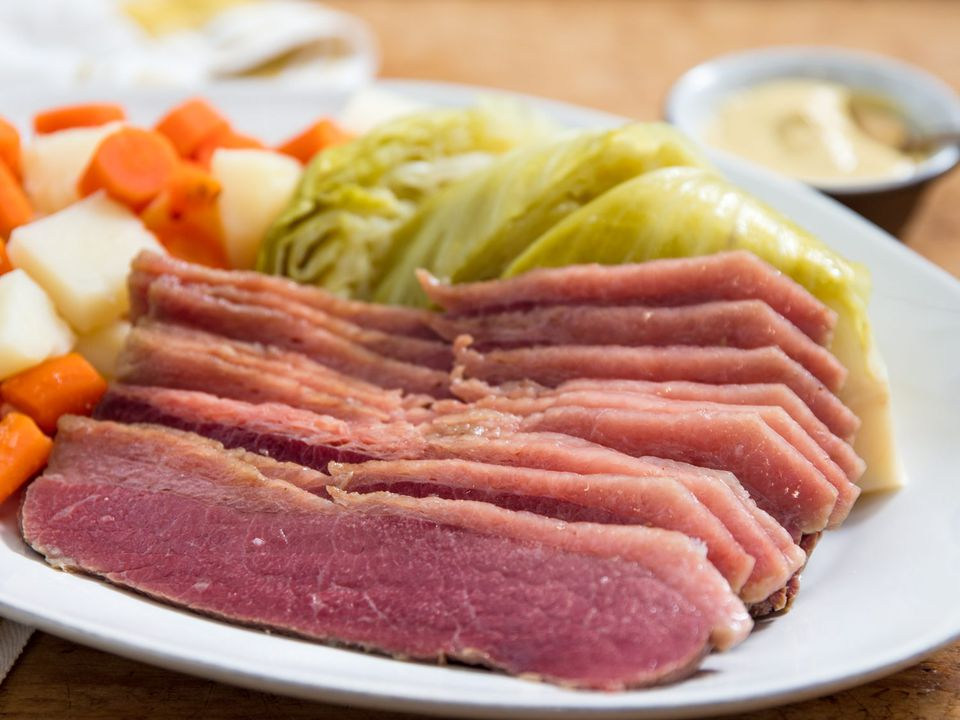 Platter of sliced corned beef and simmered cabbage, carrots, and potatoes.