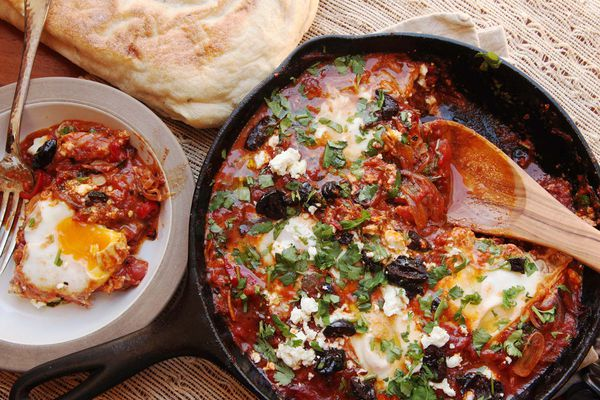 Shakshuka in a cast iron skillet, topped with parsley and olives, with a scooped single serving in a bowl and pita bread on the side.
