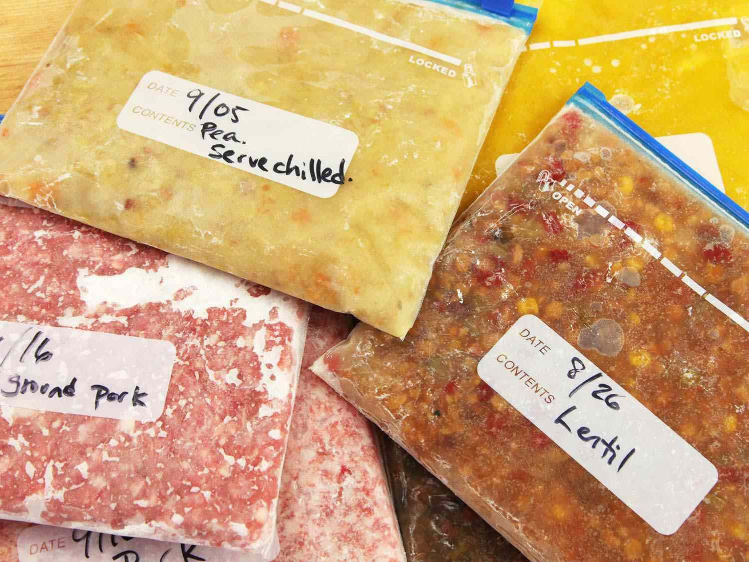 Various food items frozen flat in labeled, dated zipper-lock bags, including ground pork, lentil soup, and pea soup