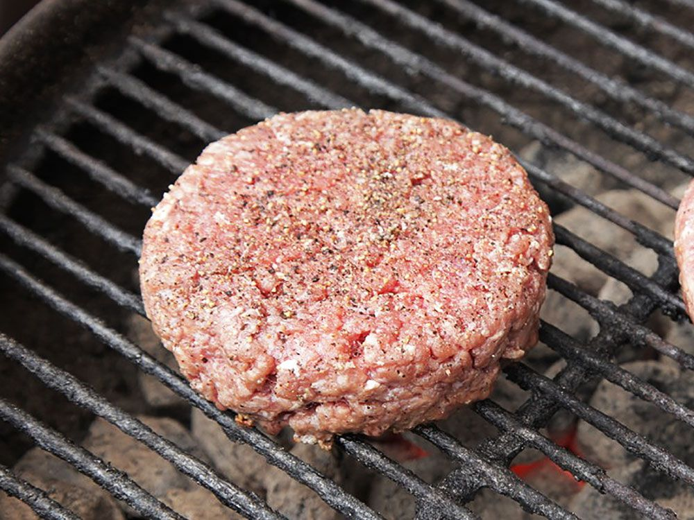 A bison burger patty on a grill.