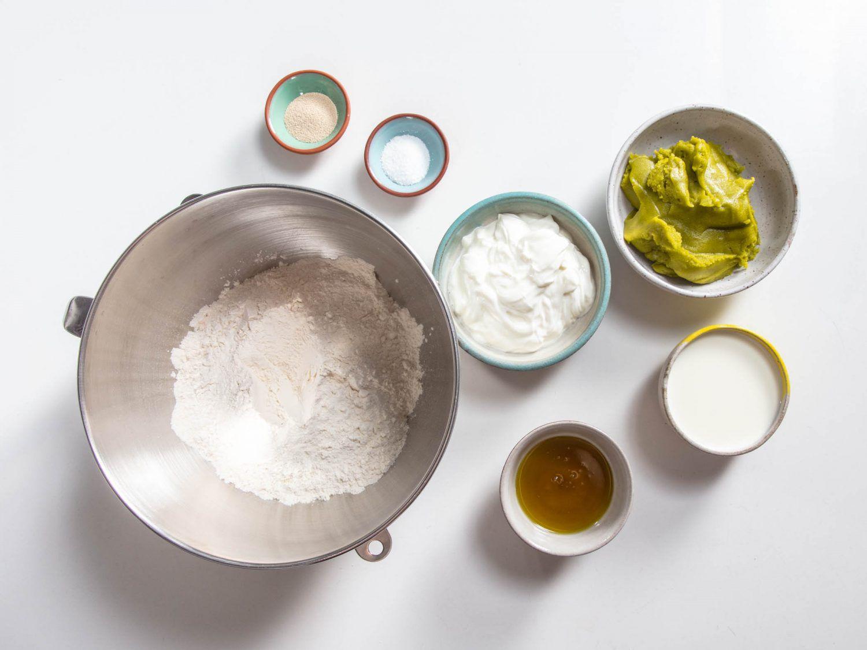 overhead shot of little bowls containing flour, salt, yeast, Greek yogurt, pistachio oil, pistachio paste, and milk