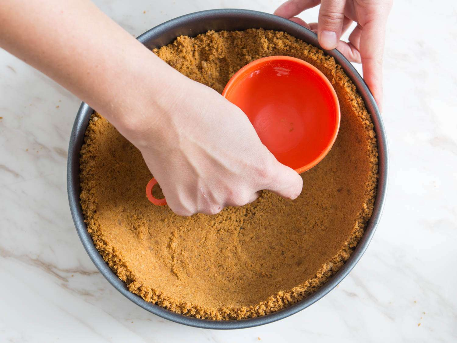 Hand using a dry measuring cup to press cookie crumb crust into the bottom and sides of a springform pan for pumpkin cheesecake.