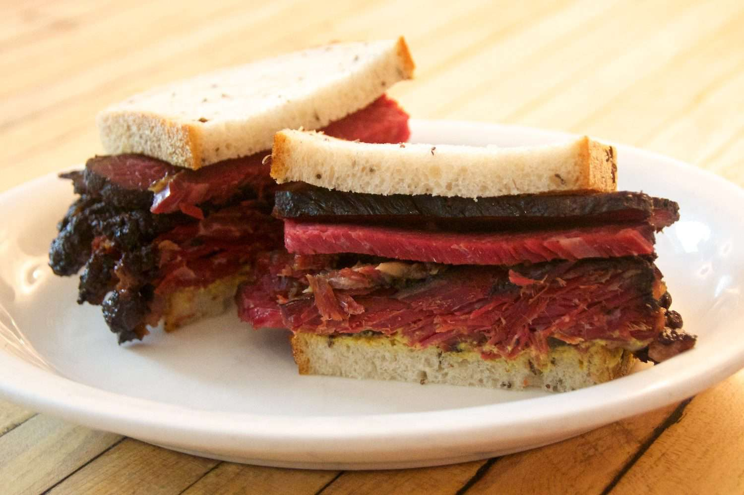 Pastrami sandwich on white serving plate.