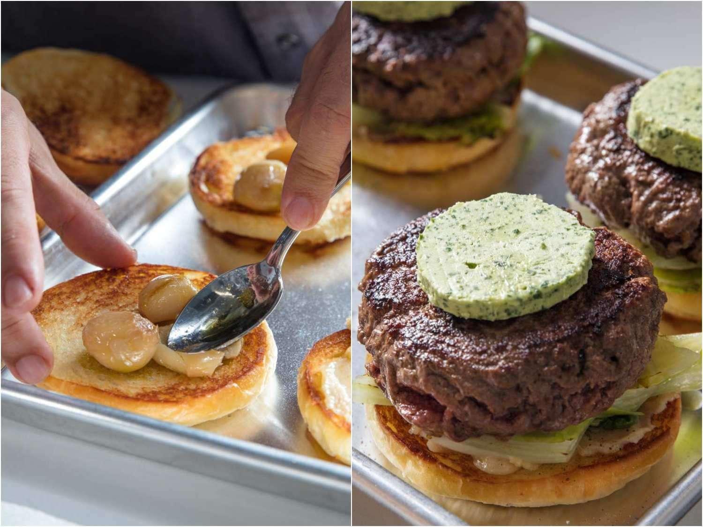 Smearing garlic confit onto burger bun, then assembling burger