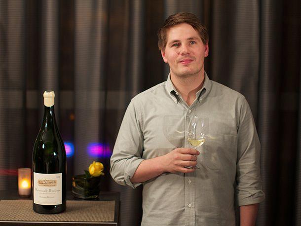 Sommelier holding glass of white wine