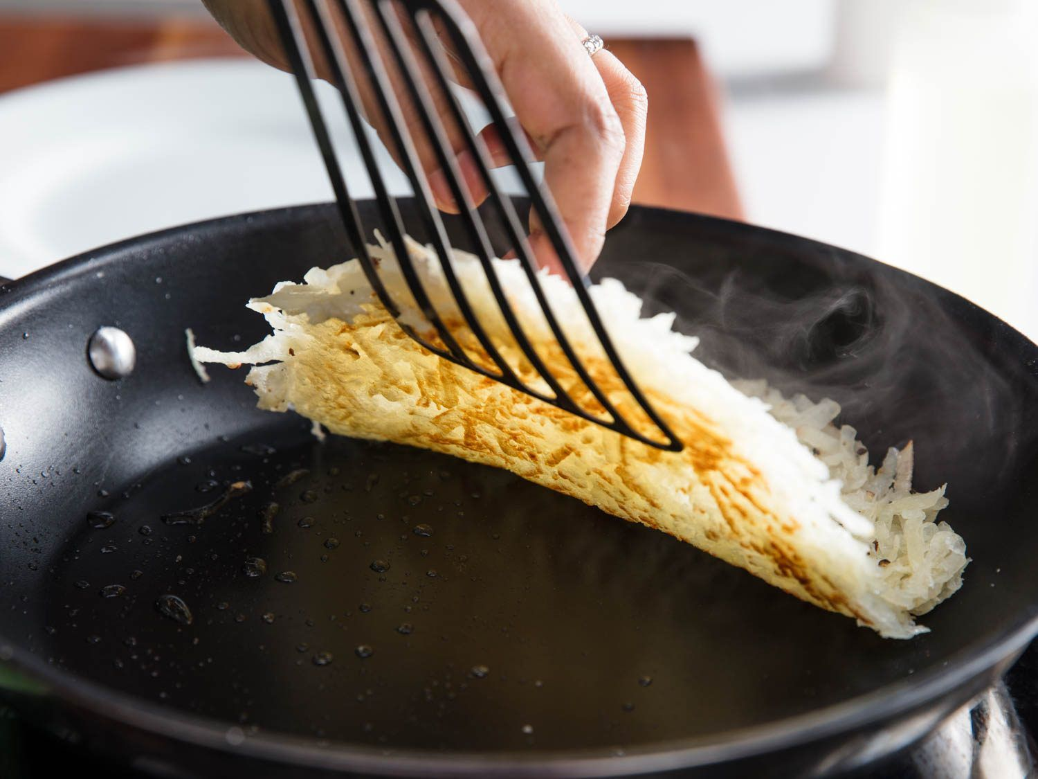 A thin metal fish spatula flipping a pile of hash browns in a skillet