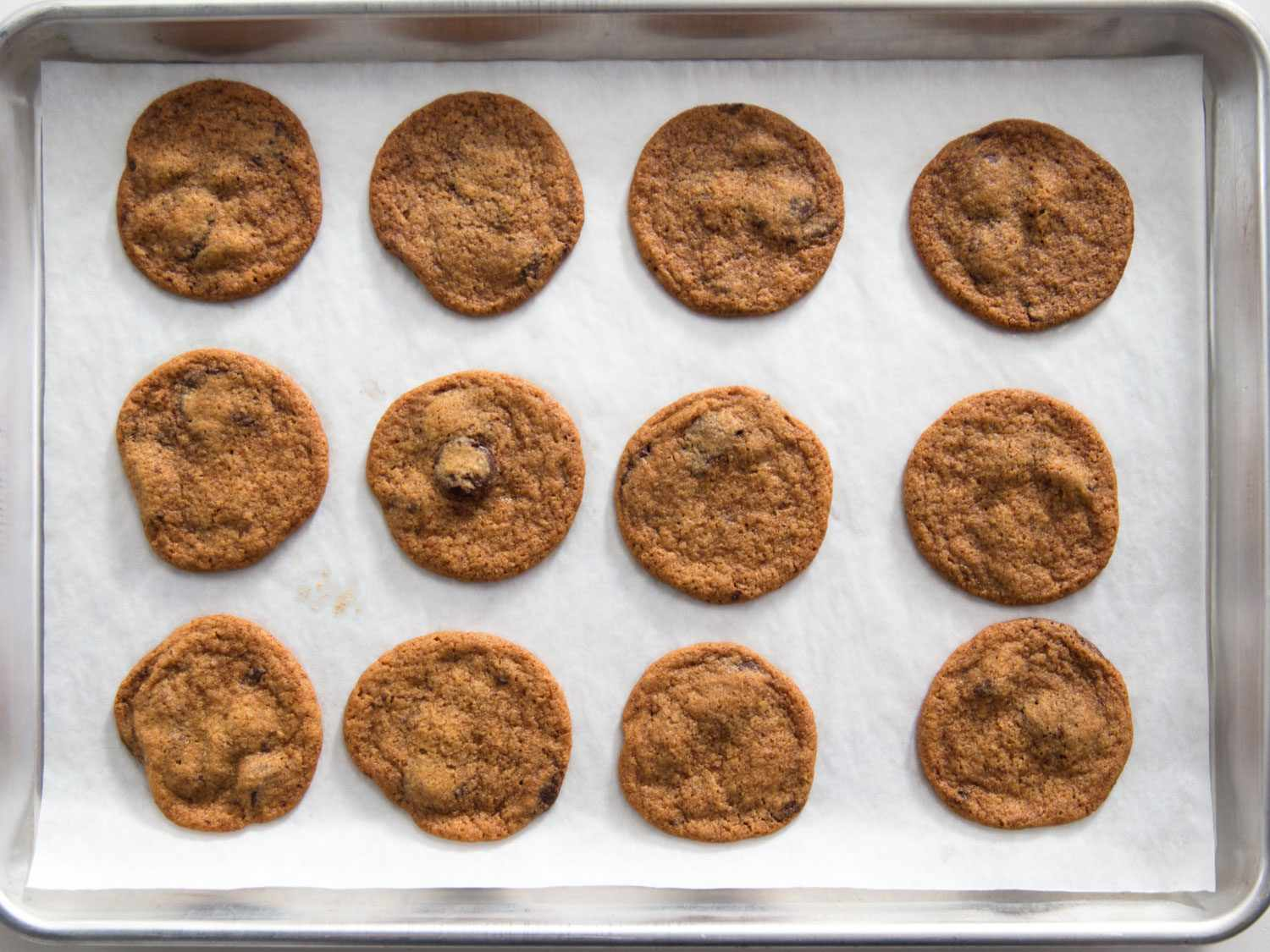 Overhead shot of thin and crispy Tate's-style chocolate chip cookies on a parchment-lined baking sheet