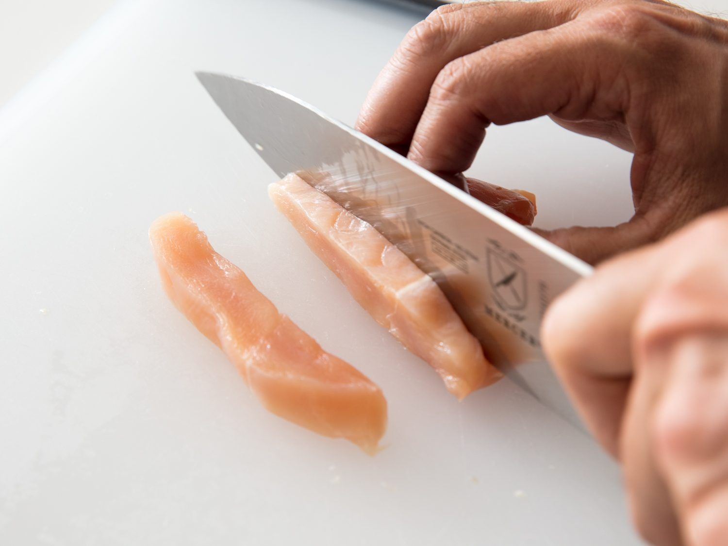 A knife slicing against the muscle grain of a chicken breast to create larger slices, which in turn will be diced into cubes, for stir-frying