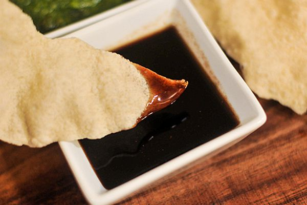 Dipping the corner of papadum into a small dish of sweet tamarind chutney