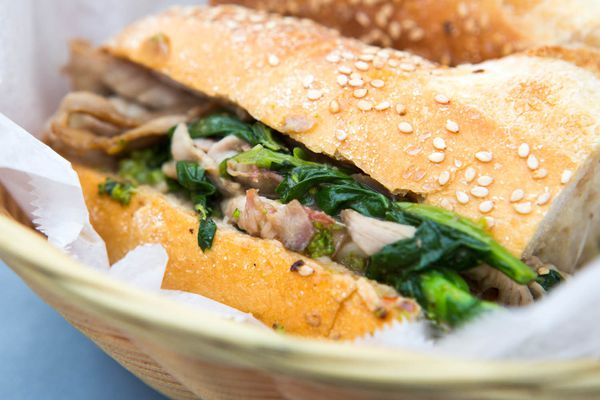 A roast pork sandwich in a basket lined with deli paper.
