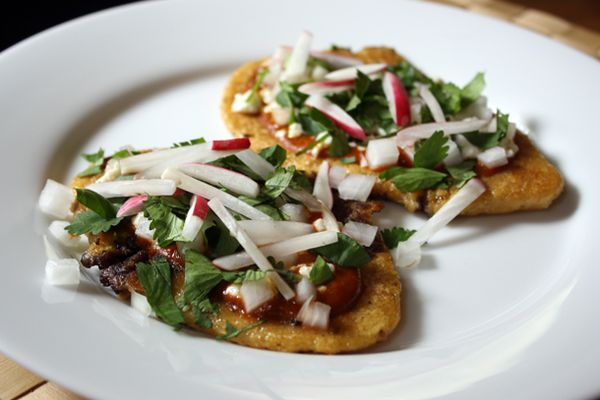 Huaraches with Black Beans and Radishes on a white plate.
