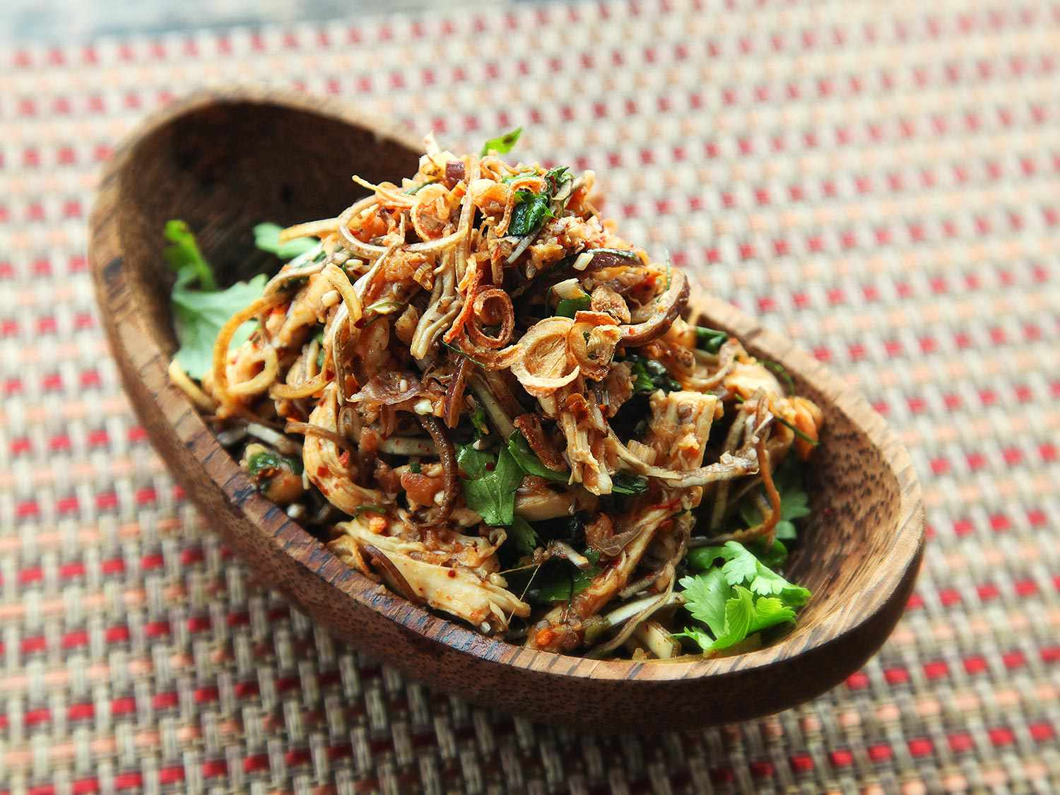 A wooden boat-shaped dish holding a Thai salad of poached chicken, banana blossom, fried shallots, fried garlic, fried lemongrass, and spicy dressing