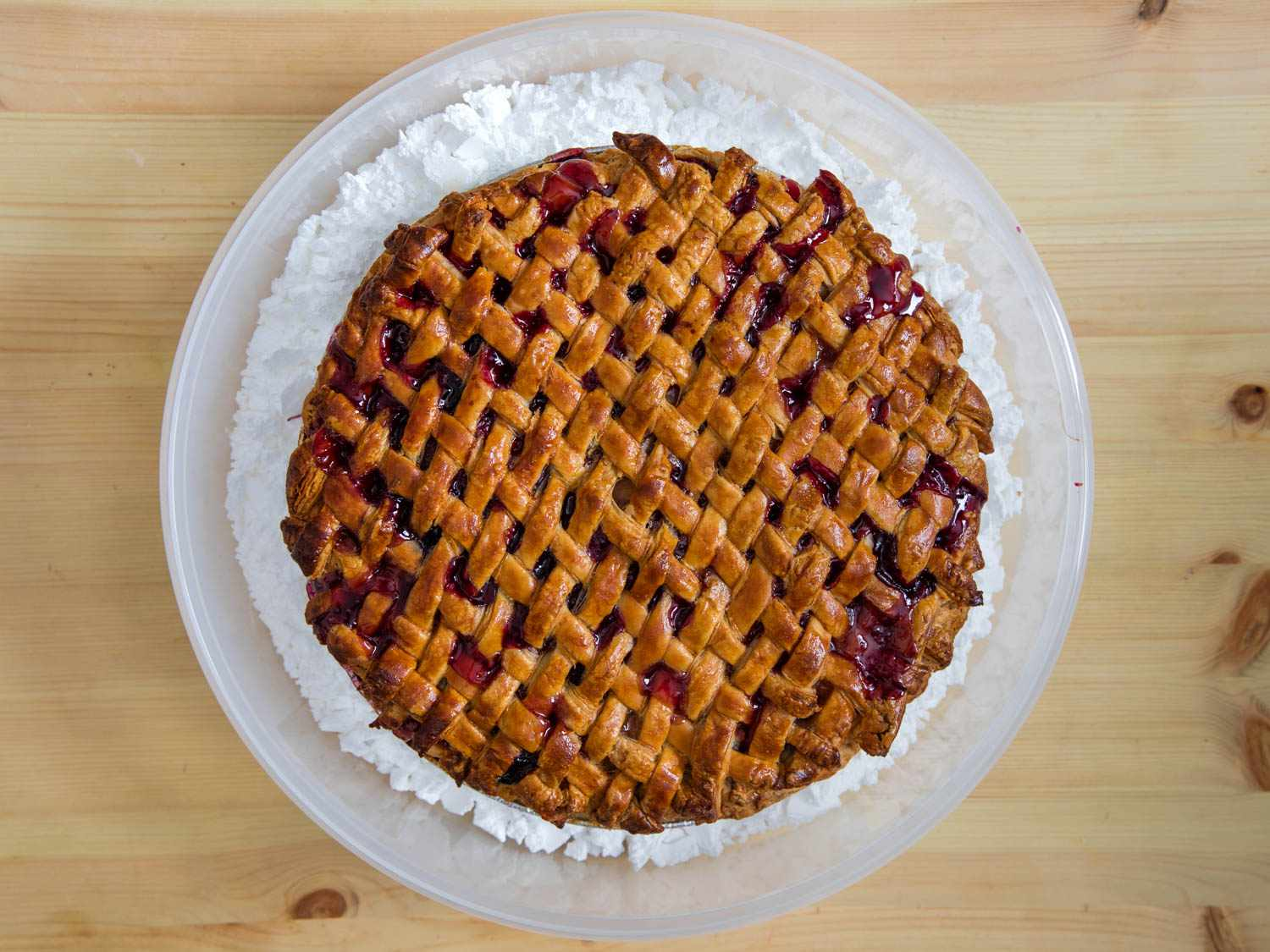 Overhead shot of a lattice-topped fruit pie on a layer of Epsom salt in a pie carrier