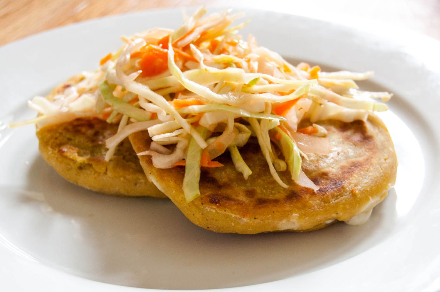 Two Salvadoran pupusas on a plate, topped with curtido, a type of slaw.