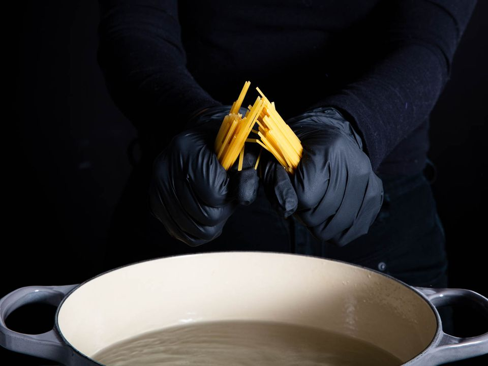 A pair of hands in black gloves breaking dry spaghetti noodles in half over an enamel cast iron pot full of boiling water.