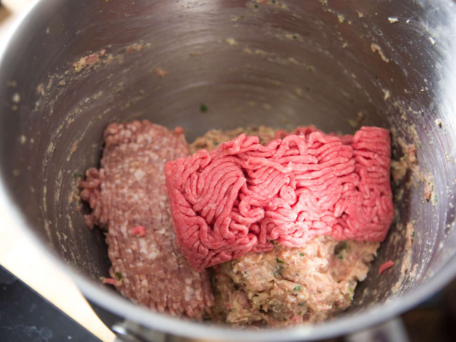 Adding remaining ground meat to emulsified meat and flavorings mixture for meatballs.