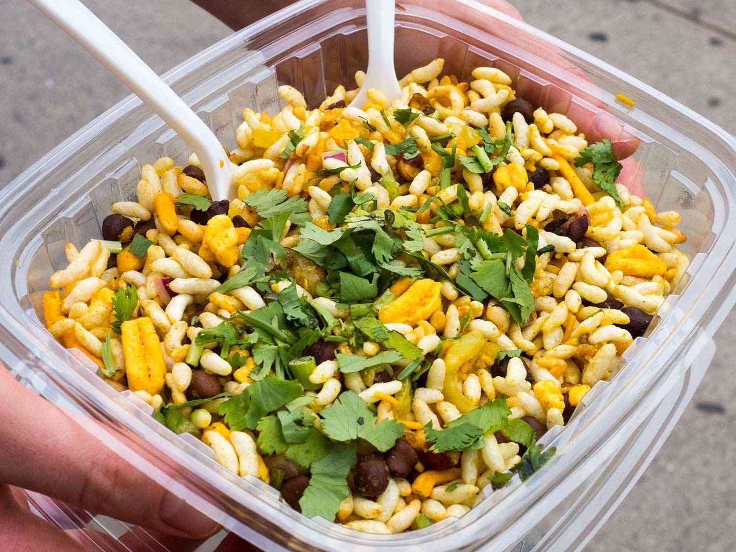 Container of jhalmuri, a mixture of puffed rice, cilantro, boiled potato, fried chickpea-flour bits, and onion.