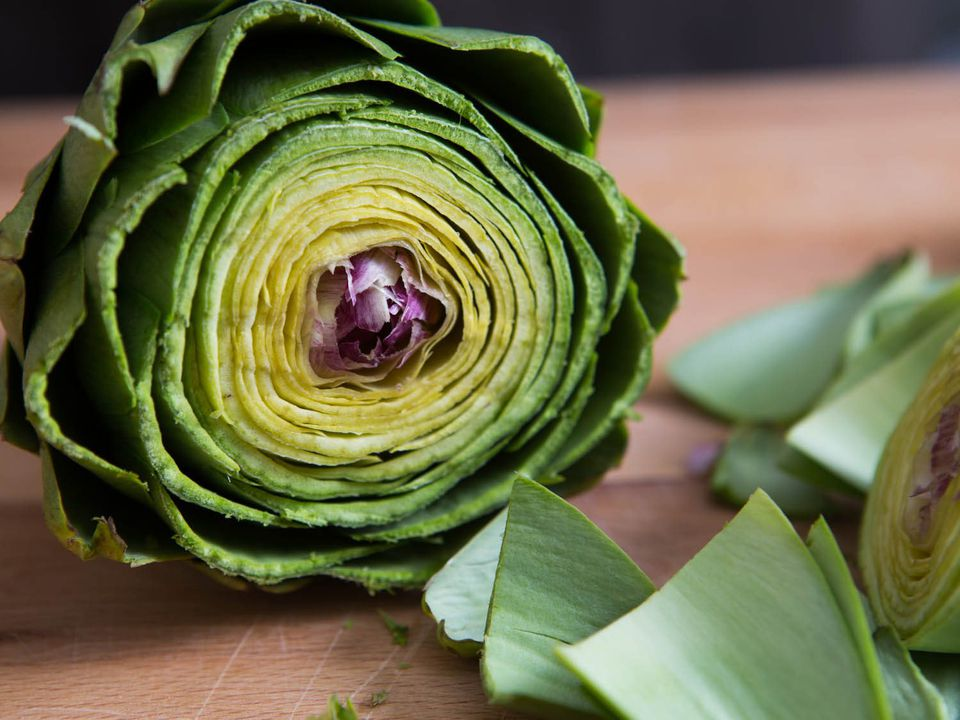 Close-up of a trimmed artichoke, with cut-off leaves (bracts) nearby