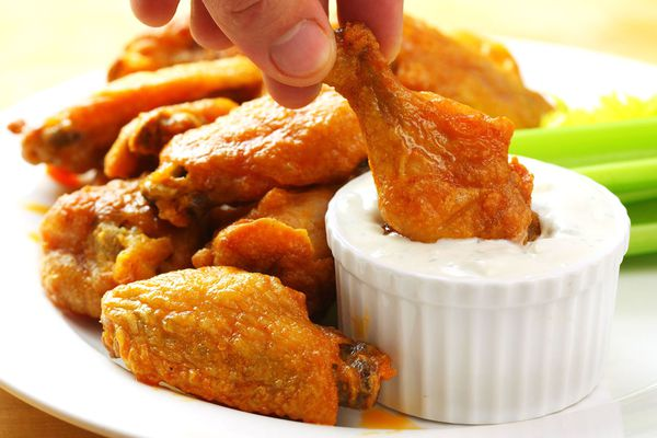 Dipping crispy baked buffalo wings into blue cheese dressing.
