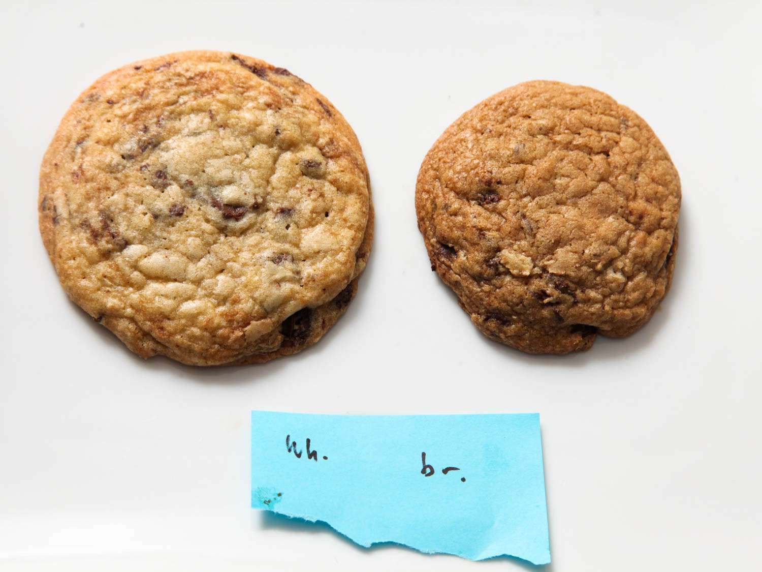 Side by side photograph showing chocolate chip cookie (left) made with all granulated sugar compared to chocolate chip cookie (right) made with all brown sugar.