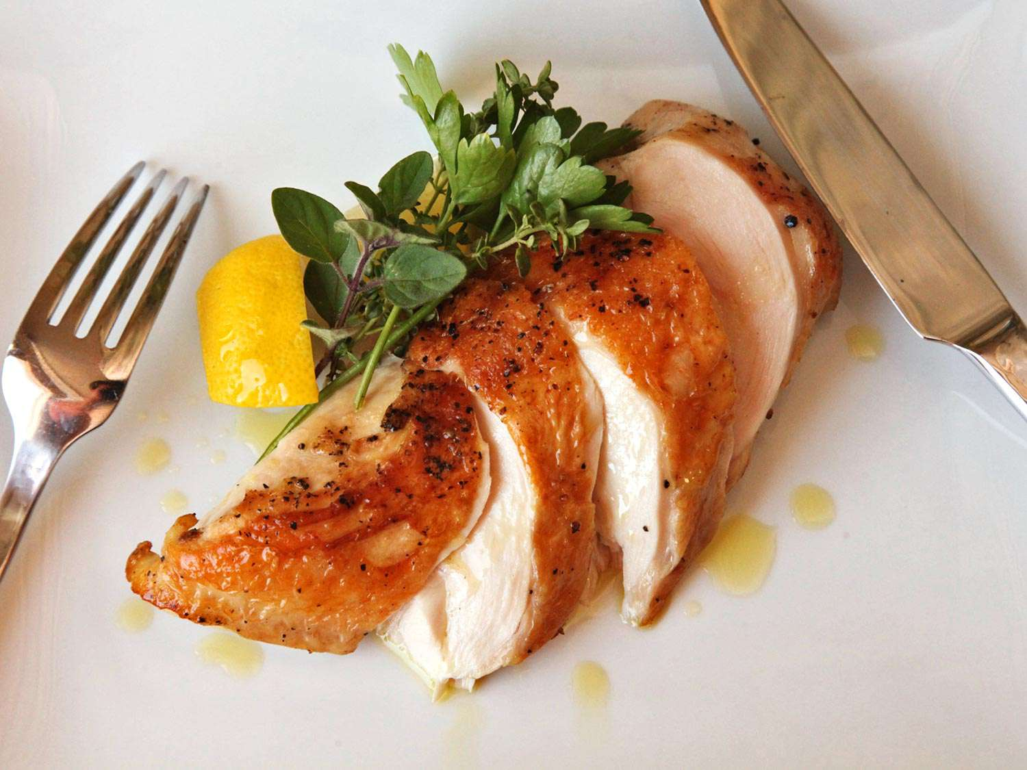 Sous vide chicken breast, cut on a bias and garnished with herbs and a lemon wedge
