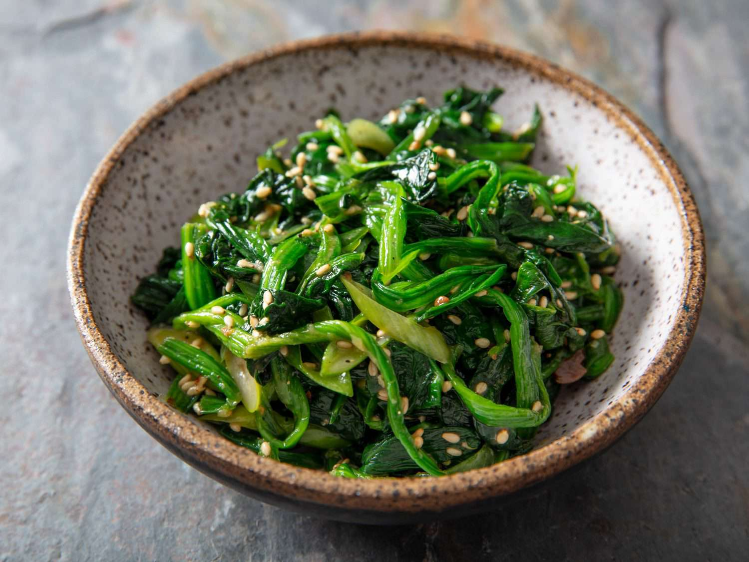 Closeup front view of a serving side dish of marinated spinach banchan.