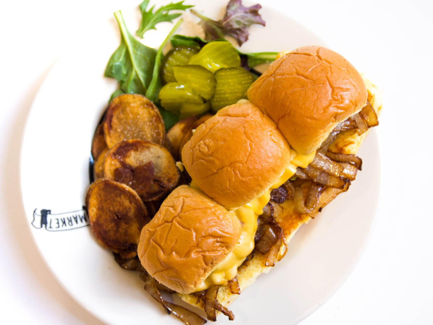 Three slider sandwiches on a plate, with chips, pickles, and greens