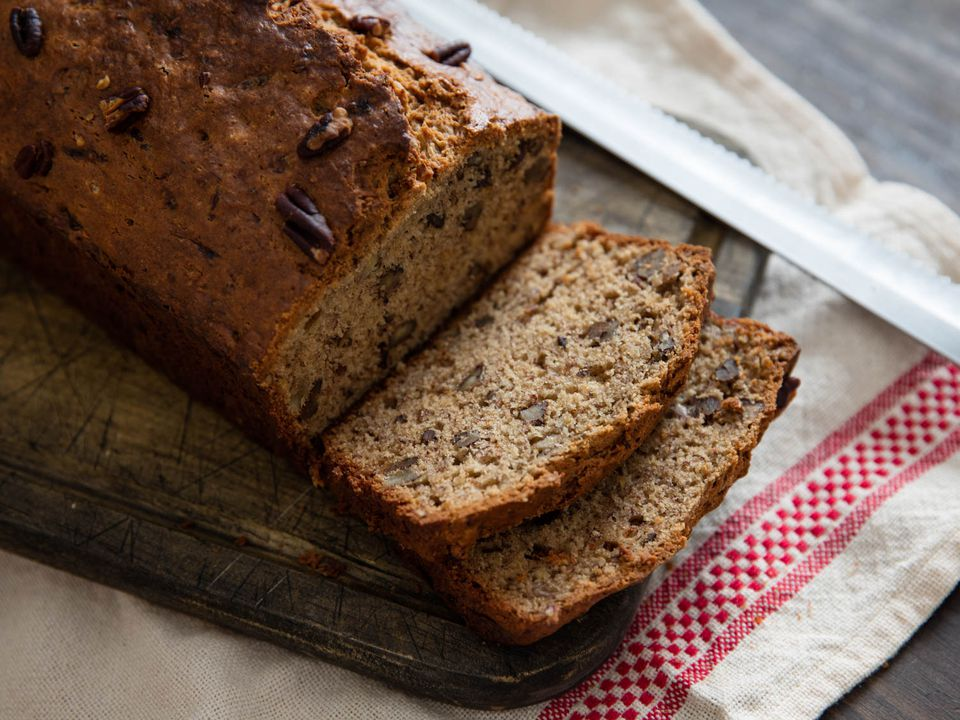 Banana bread with pecans sliced on a small wooden cutting board on top of a white kitchen towel with knife on the side.