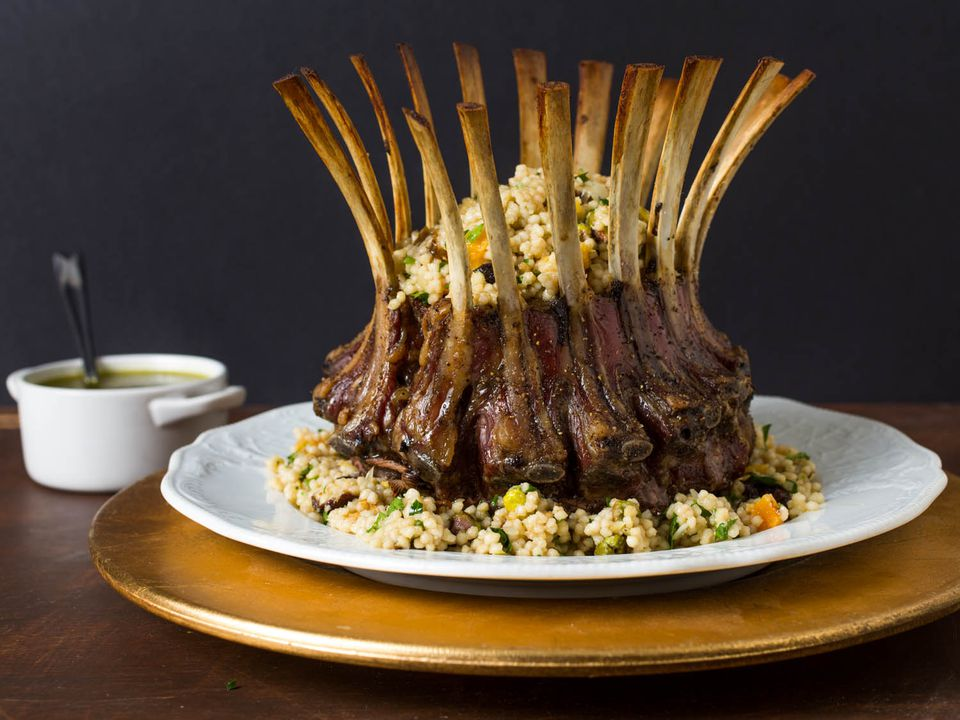 Finished crown roast of lamb with couscous stuffing, on a white plate, next to a white crock of pistachio-mint sauce