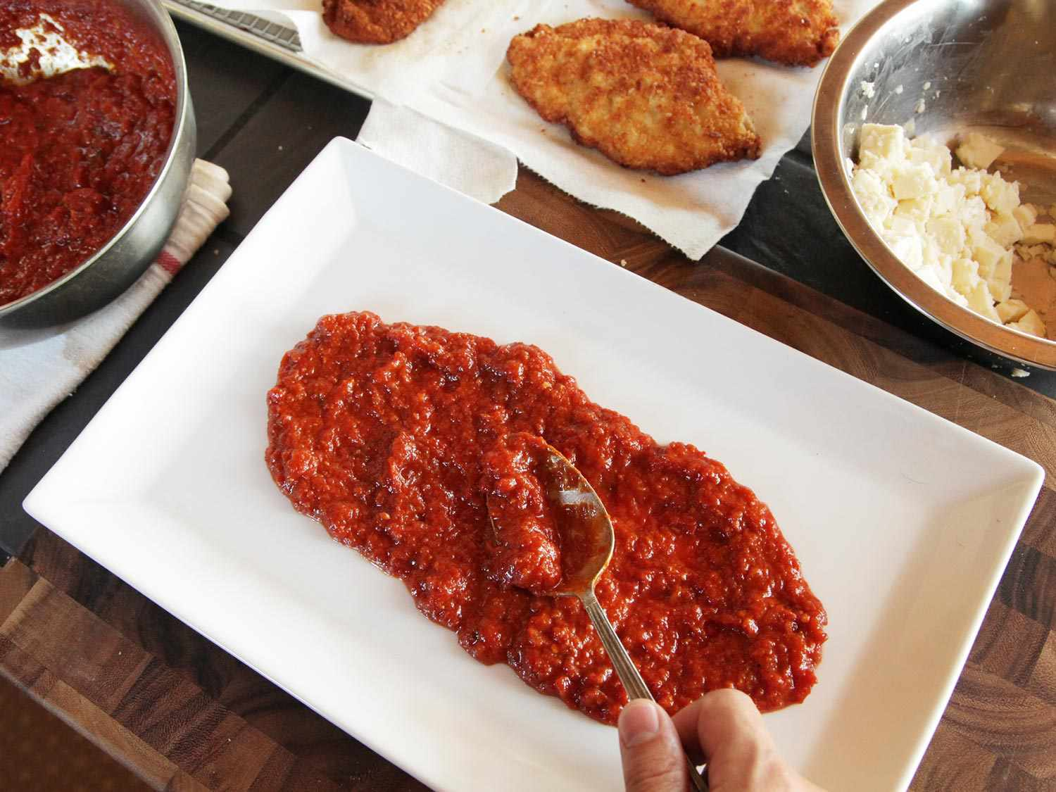 Laying down red sauce to build chicken parmesan