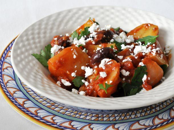Greek potato and olive stew in a white bowl