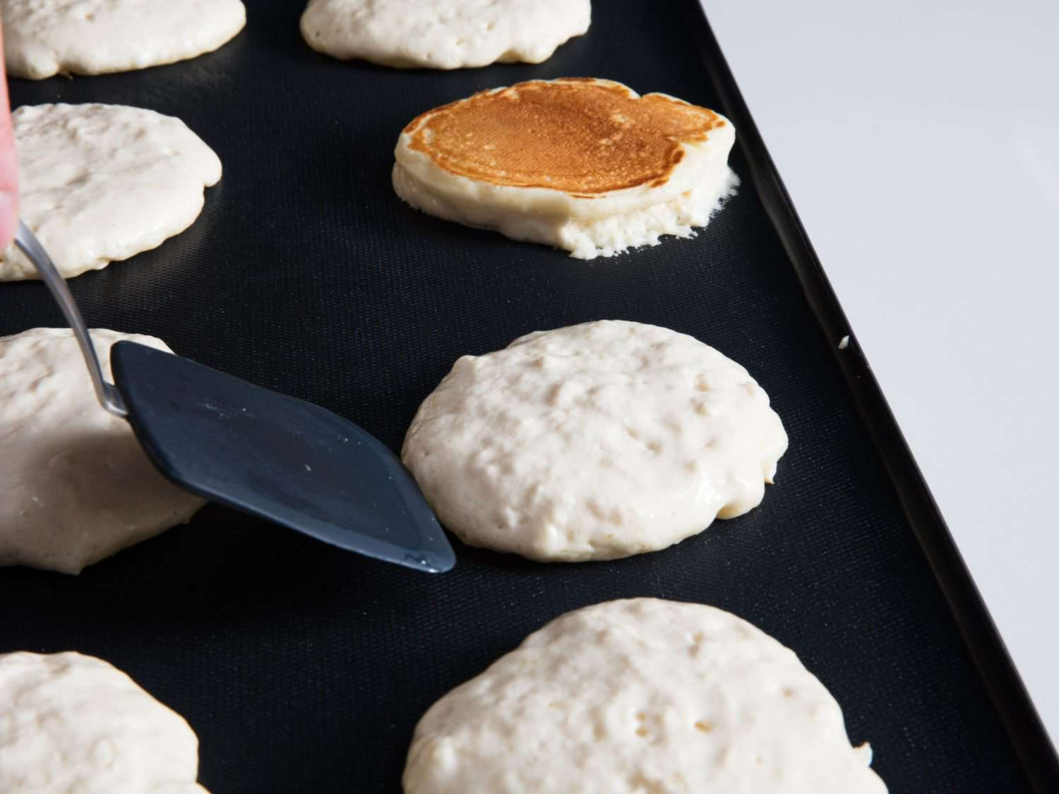 Flipping pancakes on an electric griddle.