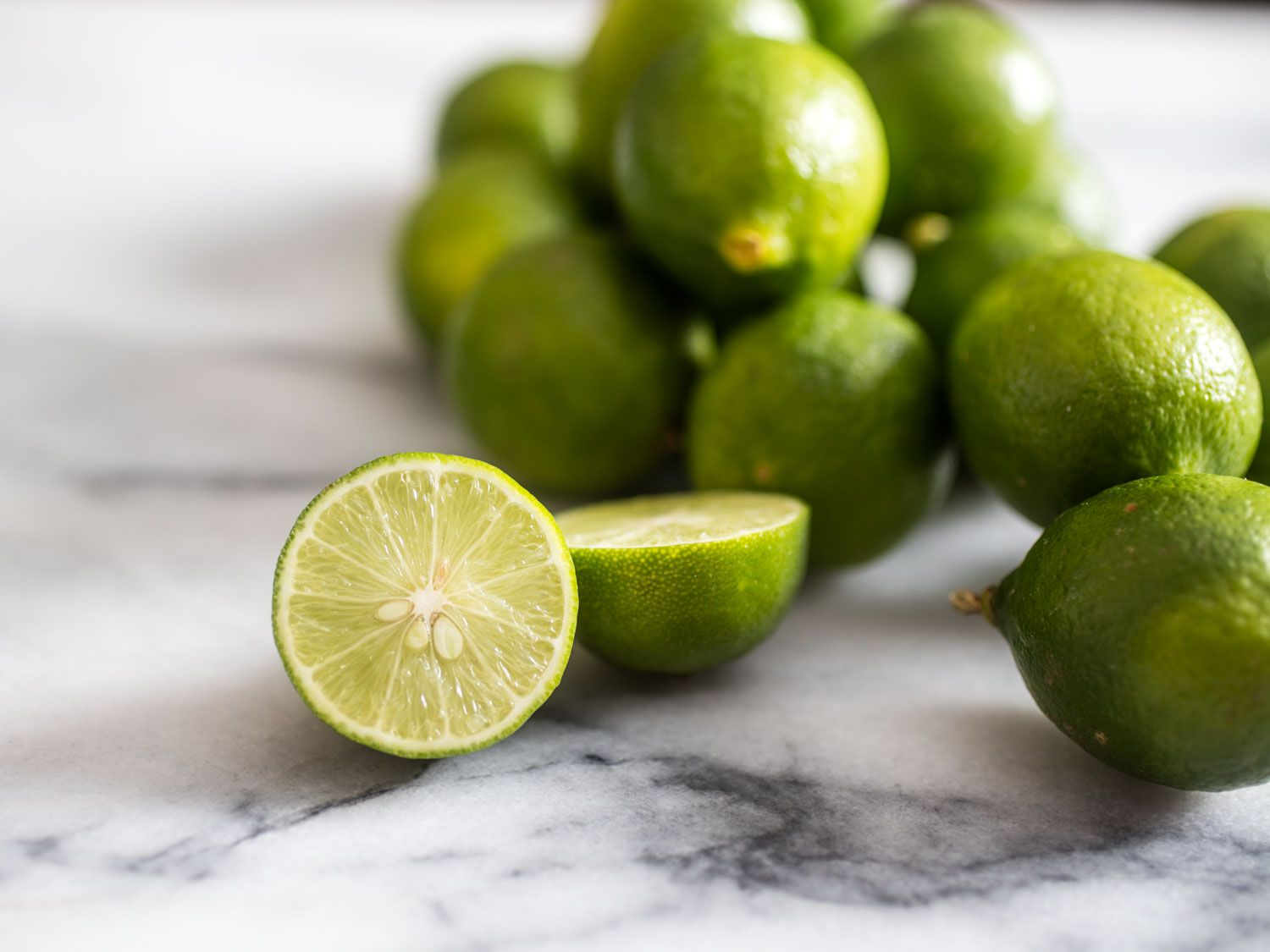 Key limes on a marble countertop. One lime is cut in half.