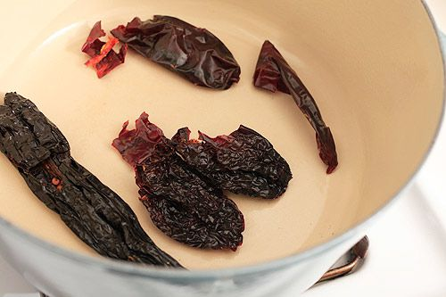a mix of dried chilies in a dutch oven